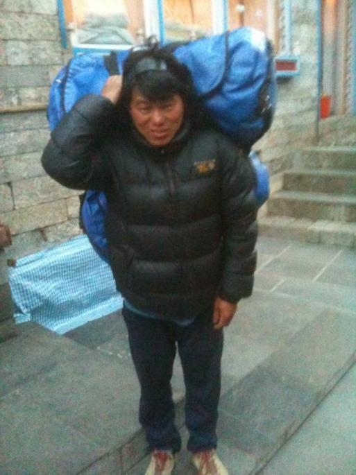 Un sherpa qui transporte deux sacs de tekking